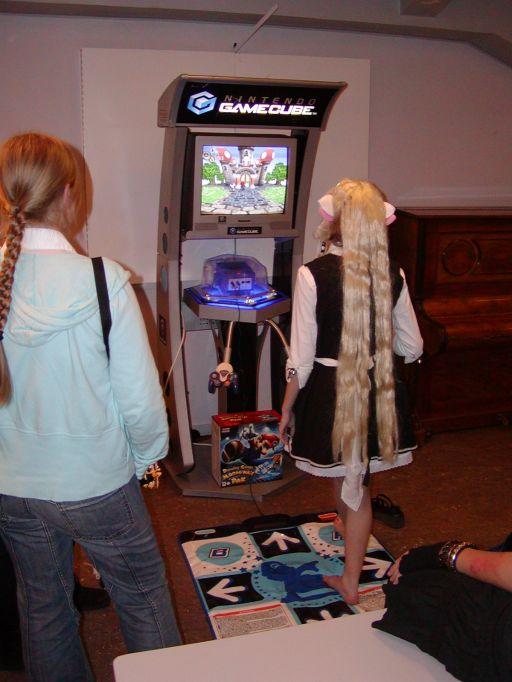 Velkommen til gameroomet på J-popcon 2005. Stedet hvor piger og drenge i alle aldre og hårfarver kunne afprøve og opleve japansk spilkultur. Her er det <a href='info/soeg?titel=Dancing Stage Mario Mix&_submit=1'>Dancing Stage Mario Mix</a> der udsættes for en cosplayer, bare fødder, animeret hår og katteører. 1/99