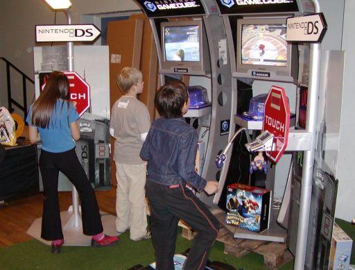 Nintendo Danmark havde valgt at støtte J-popcon ved at deltage med en stand i forhandlerrummet. <a href='info/soeg?titel=Dancing Stage Mario Mix&_submit=1'>Dancing Stage Mario Mix</a> og <a href='info/soeg?titel=Nintendogs&_submit=1'>Nintendogs</a> var glansnumrene, mens det superhurtige racerspil <a href='info/soeg?titel=F-Zero GX&_submit=1'>F-Zero GX</a> inkasserede fartbøder i fremtiden. Da DS-standerne er udformet som lygtepæle, syntes jeg der manglede noget. Jeg ledte dog forgæves blandt mængder af japanske plyds-tøjdyr. Der var ingen hunde der lettede ben. 68/99