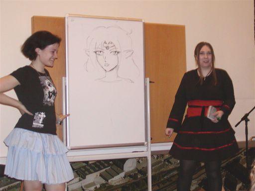 Tenna og Marie afholder Tegn Manga-Workshop for et opmærksomt publikum. Her viser de hvordan størrelsen af øjnene bestemmer alderen og alvoren hos den tegnede figur. 98/99