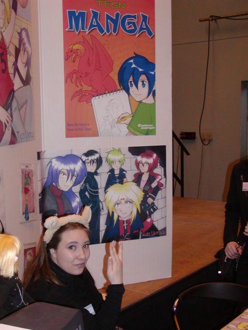 """Her sidder Marie Mortensen, med fåreører skulle jeg huske at nævne, og viser egne manga-tegninger frem. Sammen med Tenna Vinther Olsen står de bag bogen """"Tegn Manga"""" udgivet af forlaget Carlsen. Fantask meldte udsolgt af samme bog om søndagen. 14/99"""