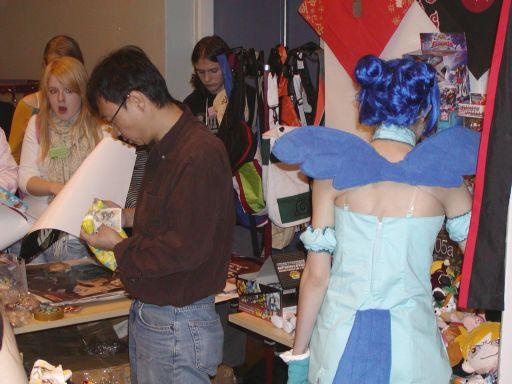 Pludselig landede der en lille fe med blåt hår og blå vinger midt i Cartoon Passions japanske merchandice-stand. Mens hun vendte ryggen til, sneg fotografen sig tæt på for at dokumentere begivenheden. Blå feer er sjældne og pigen til venstre ser måbende til. 58/99