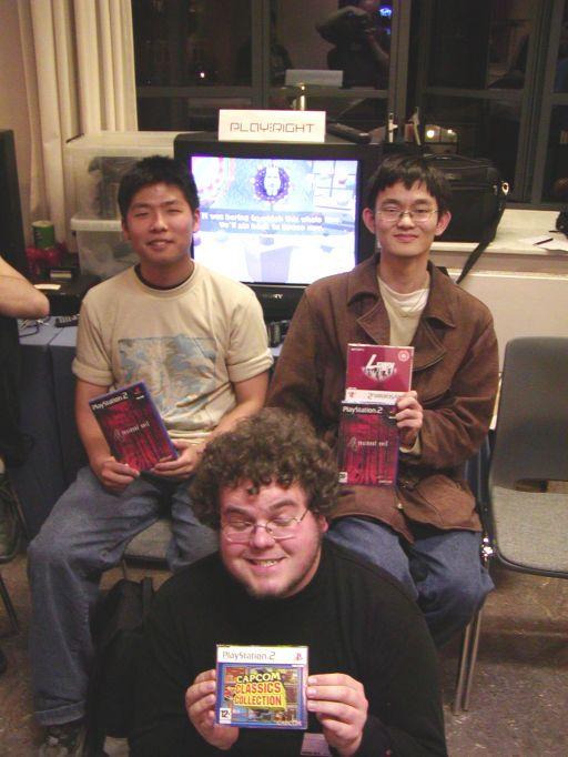 """Og her sidder de så, i en stor bunke, vinderne af den store Play:Right-konkurrence om titlen som """"Senior Katamari Master-of-all-Cosmos"""". Vinderen blev Dong Trieu Do til højre og andenpladsen gik til Samuel Korn til venstre. Et spritnyt Resident Evil 4 til dem begge og en ekstra Killer 7 til Dong. Trediepladsen gik til Alexander Munck, med øjnene lukket, som blev retroficeret med et eksemplar af Capcom Classic Collection. 81/99"""